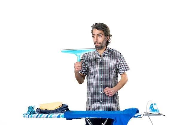 전면보기 젊은 남성 흰색 배경에 다림질 판 뒤에 청소기 브러시를 들고 철 세탁 가사 옷 기계 집