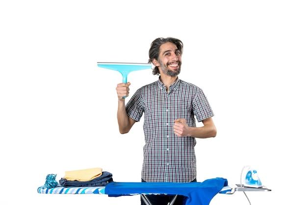 흰색 바탕에 다리미판 뒤에 청소기 브러시를 들고 있는 젊은 남성 철 세탁 옷 집 가사 깨끗한 기계