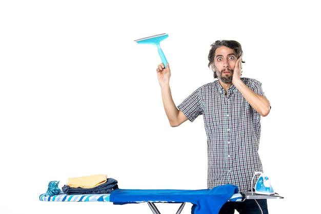 Вид спереди молодой мужчина держит щетку для чистки за гладильной доской удивлен на светлом фоне дома утюг прачечная одежда чистая машина работа по дому