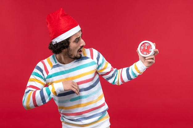 Front view young male holding clocks on red wall new year holidays red male