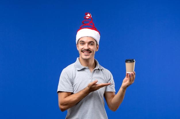 青い壁にコーヒーカップを保持している若い男性の正面図新年の男性の休日