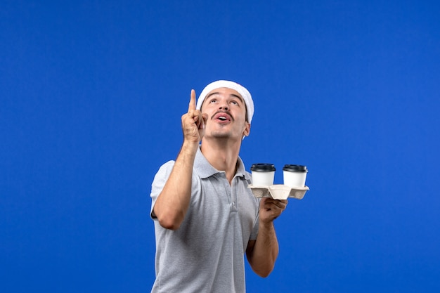 Front view young male holding coffee cups on blue wall emotion coffee blue human
