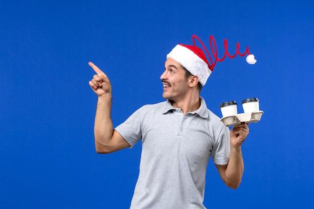 青い壁の感情人間のコーヒーブルーにコーヒーカップを保持している正面図若い男性