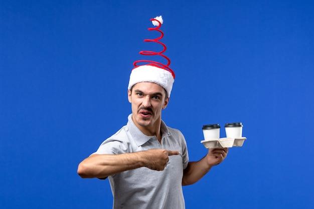 Вид спереди молодого мужчины, держащего кофейные чашки на синем полу, эмоция мужского нового года