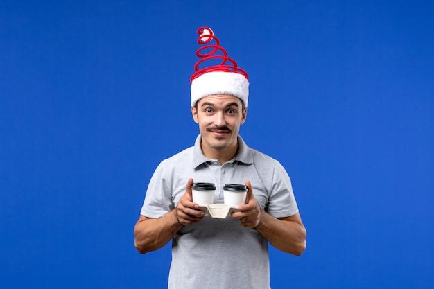 青い壁の感情の男性の新年にコーヒーカップを保持している正面図若い男性