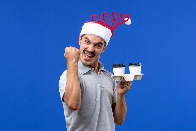 青い壁の感情コーヒーブルー人間にコーヒーカップを保持している正面図若い男性