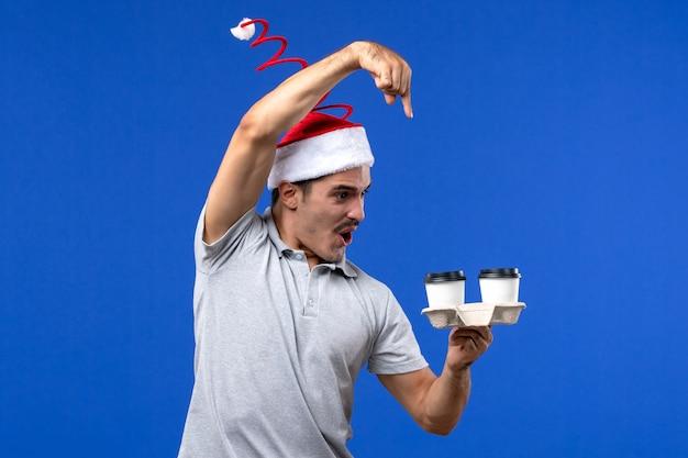 Вид спереди молодого мужчины, держащего кофейные чашки на синей стене, эмоции человека, кофе синий