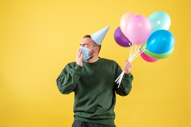 노란색 배경에 마스크에 다채로운 풍선을 들고 전면보기 젊은 남성
