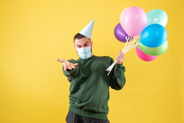 Front view young male holding colorful balloons in mask on yellow background