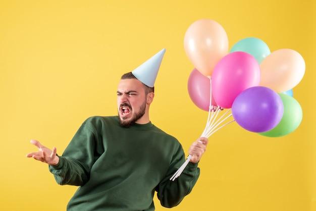 Вид спереди молодой мужчина держит разноцветные шары на желтом фоне