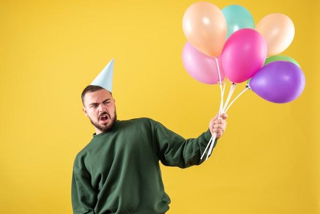 黄色の背景にカラフルな風船を保持している正面図若い男性