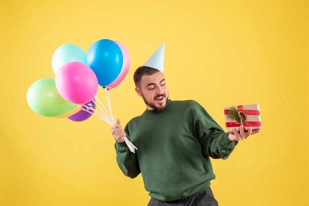 Front view young male holding colorful balloons and present on a yellow background