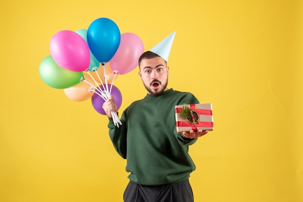 Front view young male holding colorful balloons and present on the yellow background