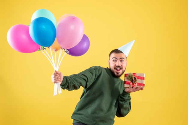 Front view young male holding colorful balloons and present on yellow background