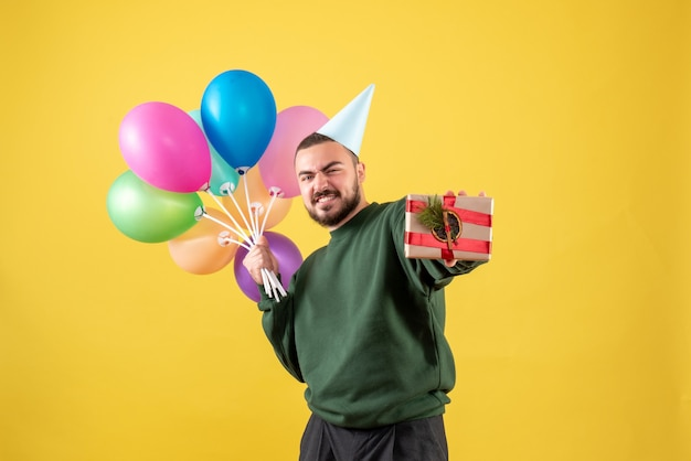 Front view young male holding colorful balloons and present on yellow