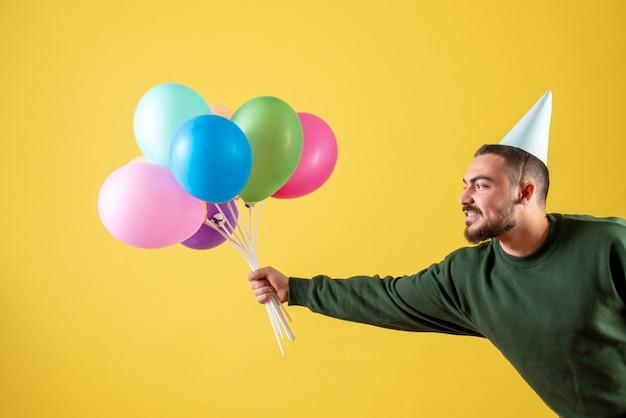 Vista frontale giovane maschio che tiene palloncini colorati su sfondo giallo