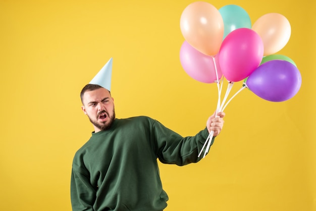 Front view young male holding colorful balloons on yellow background