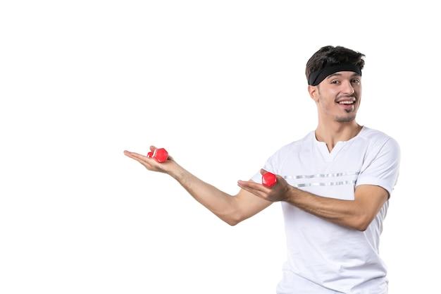 正面図白い背景色のダンベルを保持している若い男性ボディフィットダイエット健康アスリートヨガ人間のライフスタイルスポーツ