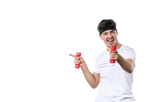 正面図白い背景にダンベルを保持している若い男性ボディフィットダイエット健康アスリートヨガ人間の色のライフスタイル