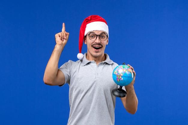 Vista frontale giovane maschio che tiene globo terrestre sulla vacanza piano blu viaggio aereo umano