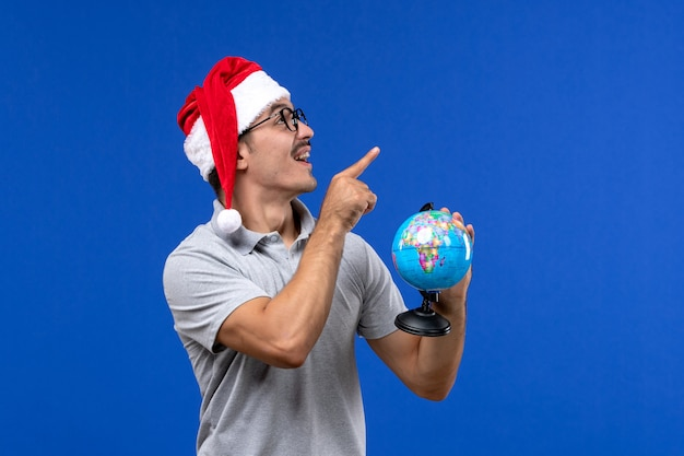 Front view young male holding earth globe on a blue wall plane human vacation trip