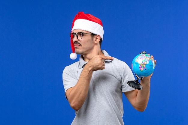 Front view young male holding earth globe on a blue wall plane vacation male trip