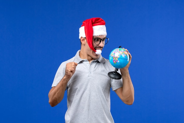 Front view young male holding earth globe on a blue wall plane vacation trip male