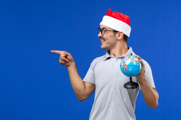 블루 데스크 여행 인간의 비행기 휴가에 지구 글로브를 들고 전면보기 젊은 남성