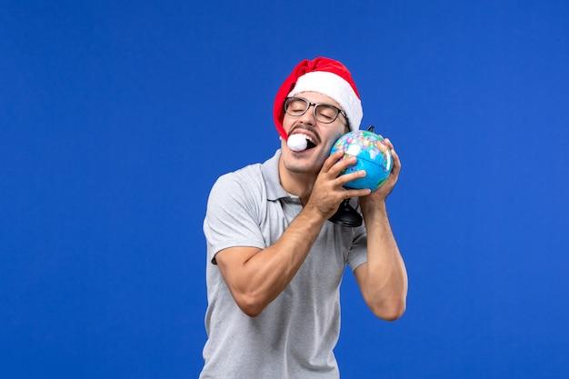 青い壁の旅行飛行機休暇の男性に地球儀を保持している正面図若い男性