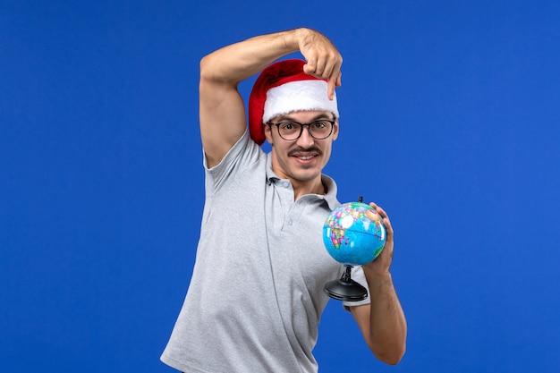 青い壁の平面の人間の休暇旅行で地球儀を保持している正面図若い男性