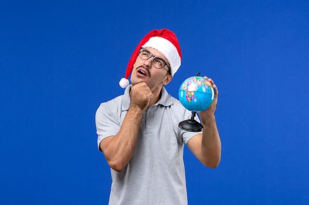 Вид спереди молодой мужчина, держащий земной шар на синей стене, путешествие на человеческом самолете, отдых