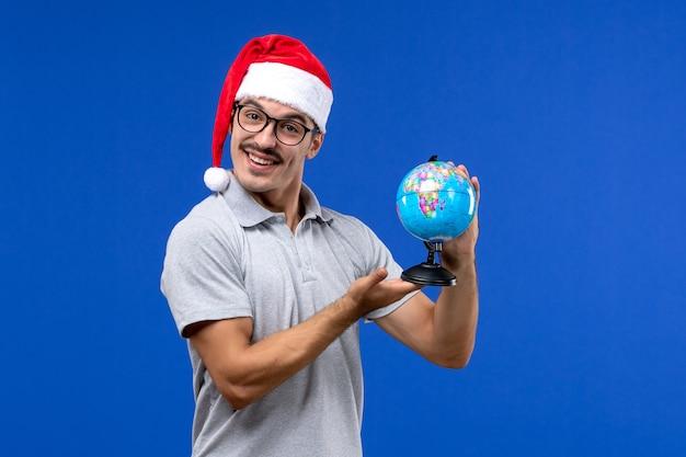 Вид спереди молодого мужчины, держащего земной шар на синей стене, путешествие на человеческих самолетах в отпуск