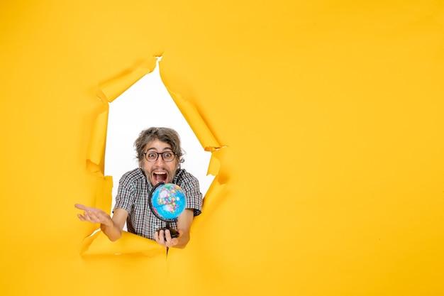 Вид спереди молодой мужчина, держащий земной шар на желтом фоне, цветная рождественская планета, праздник, мир, страна, эмоция