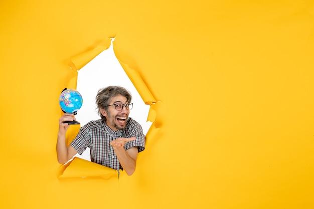 Vista frontale giovane maschio che tiene il globo terrestre su sfondo giallo colore natale pianeta vacanza mondo paese emozione