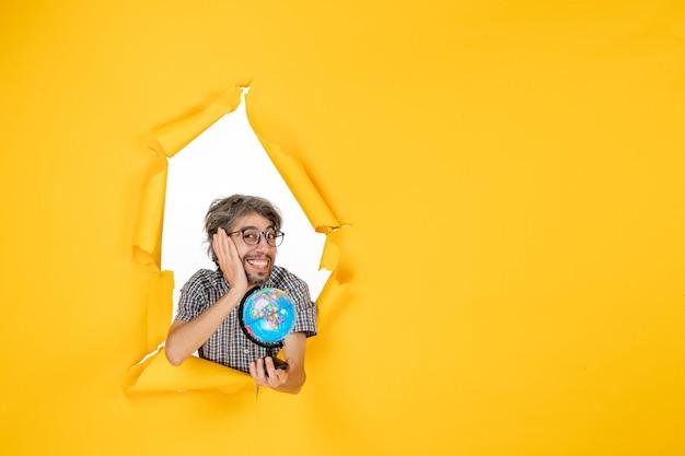 Vista frontale giovane maschio che tiene il globo terrestre su sfondo giallo colore natale pianeta vacanze mondo paese emozione