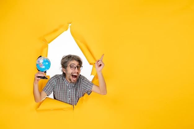 Vista frontale giovane maschio che tiene il globo terrestre su sfondo giallo colore emozione natale pianeta vacanza mondo paese