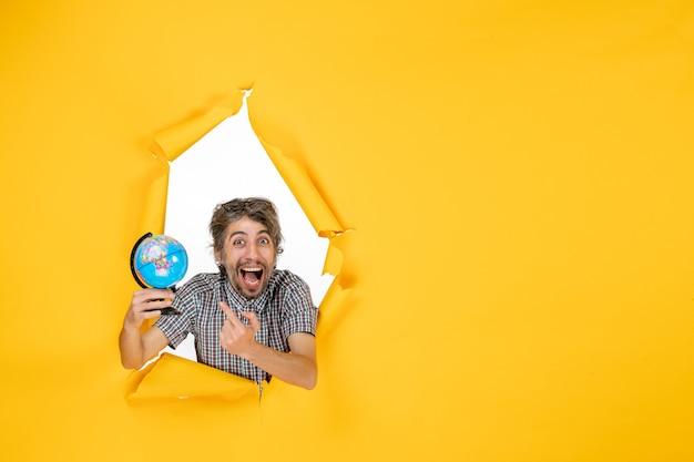 Vista frontale giovane maschio che tiene il globo terrestre sullo sfondo giallo emozione pianeta natale vacanze paese mondo colore