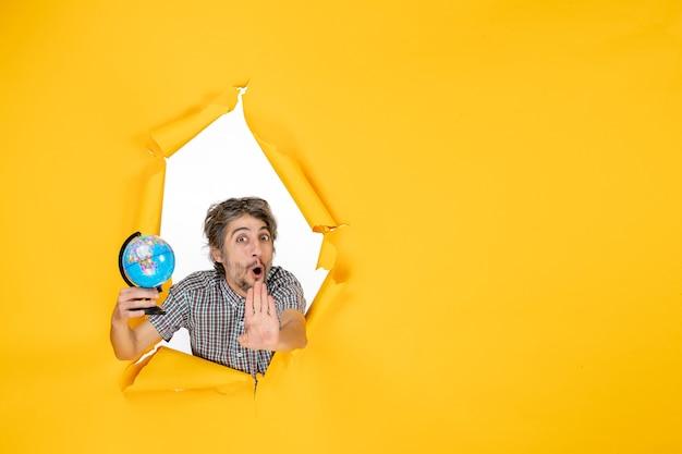 Vista frontale giovane maschio che tiene il globo terrestre su sfondo giallo emozione pianeta vacanza paese mondo colore