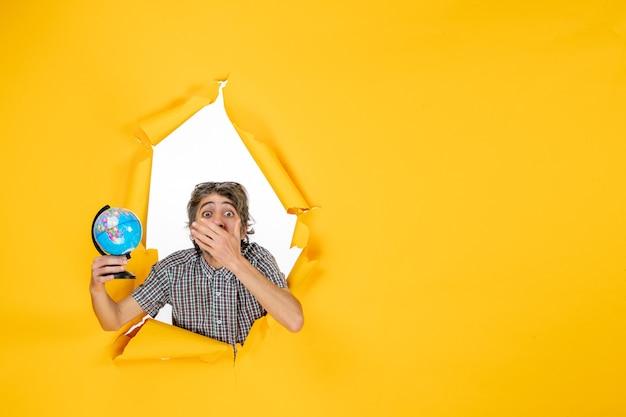 Vista frontale giovane maschio che tiene il globo terrestre su sfondo giallo emozione vacanza natale paese mondo colore pianeta