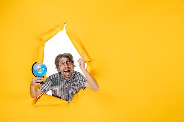 Vista frontale giovane maschio che tiene il globo terrestre su sfondo giallo vacanza emozione natale paese mondo colore