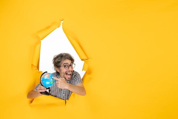 Vista frontale giovane maschio che tiene il globo terrestre su sfondo giallo mondo paese emozioni natale colore pianeta vacanza