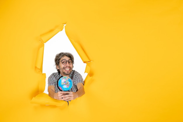 Vista frontale giovane maschio che tiene il globo terrestre su sfondo giallo emozione vacanza mondiale natale paese pianeta