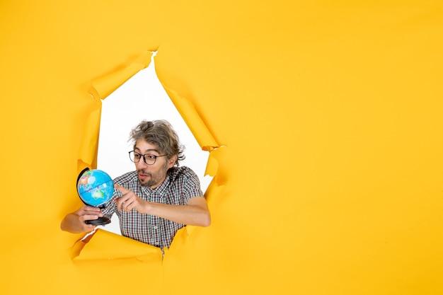 Vista frontale del giovane maschio che tiene il globo terrestre sulla parete gialla