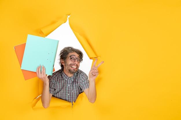 Vista frontale giovane maschio in possesso di file su sfondo giallo colore ufficio vacanza lavoro natale lavoro emozione