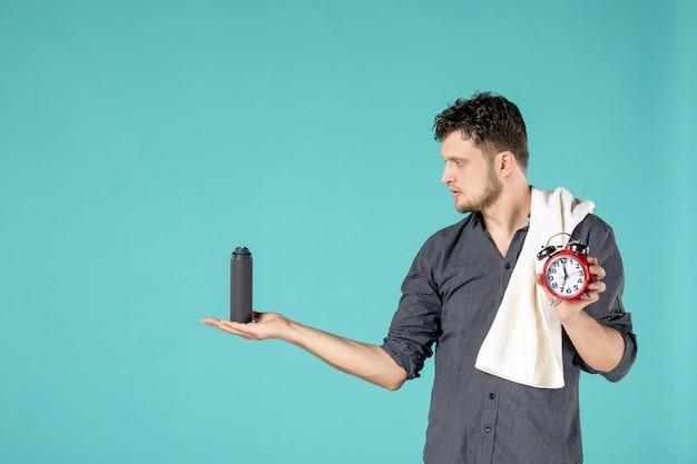 Вид спереди молодой мужчина держит пену для бритья и часы на синем фоне