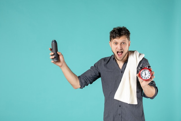 Front view young male holding foam for shaving and a clock on blue background