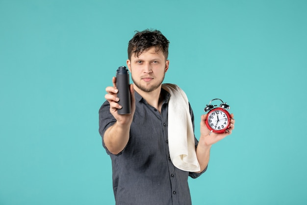 Front view young male holding foam for shaving and clock on blue background