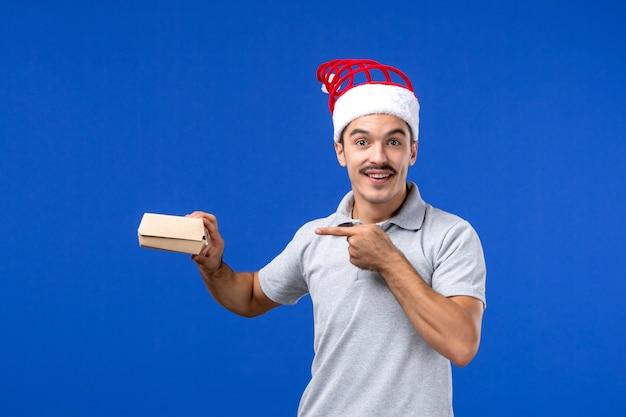 Giovane maschio che tiene pacchetto dell'alimento di vista frontale sul lavoro di servizio maschio dell'alimento della parete blu