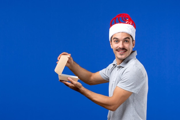 Vista frontale giovane maschio che tiene pacchetto di cibo sul lavoro di servizio di cibo maschio muro blu