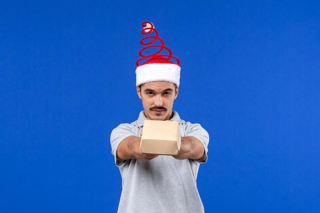 Vista frontale giovane maschio che tiene il pacchetto di cibo sulla parete blu maschio lavoro servizio di ristorazione umano